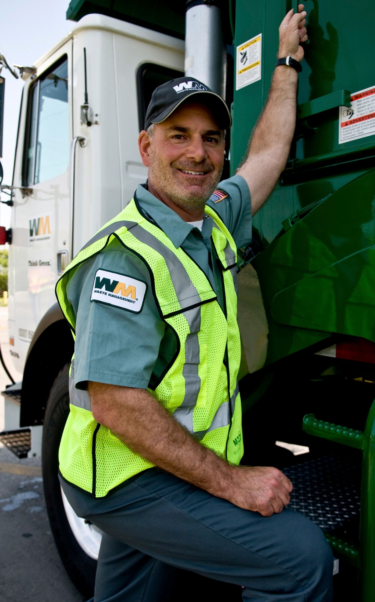 Waste Management COO Larry O'Donnell in uniform next to a truck