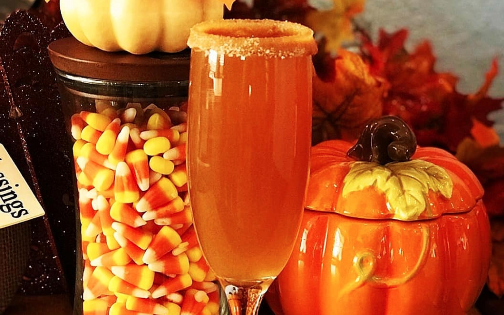 a champagne flute with an apple cider mimosa in it, a pumpkin-shaped jar behind it, and a jar of candy corn