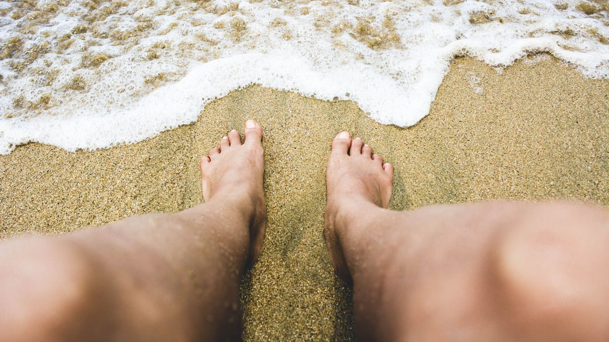 Bare legs on the sand illustrating a nudist beach.