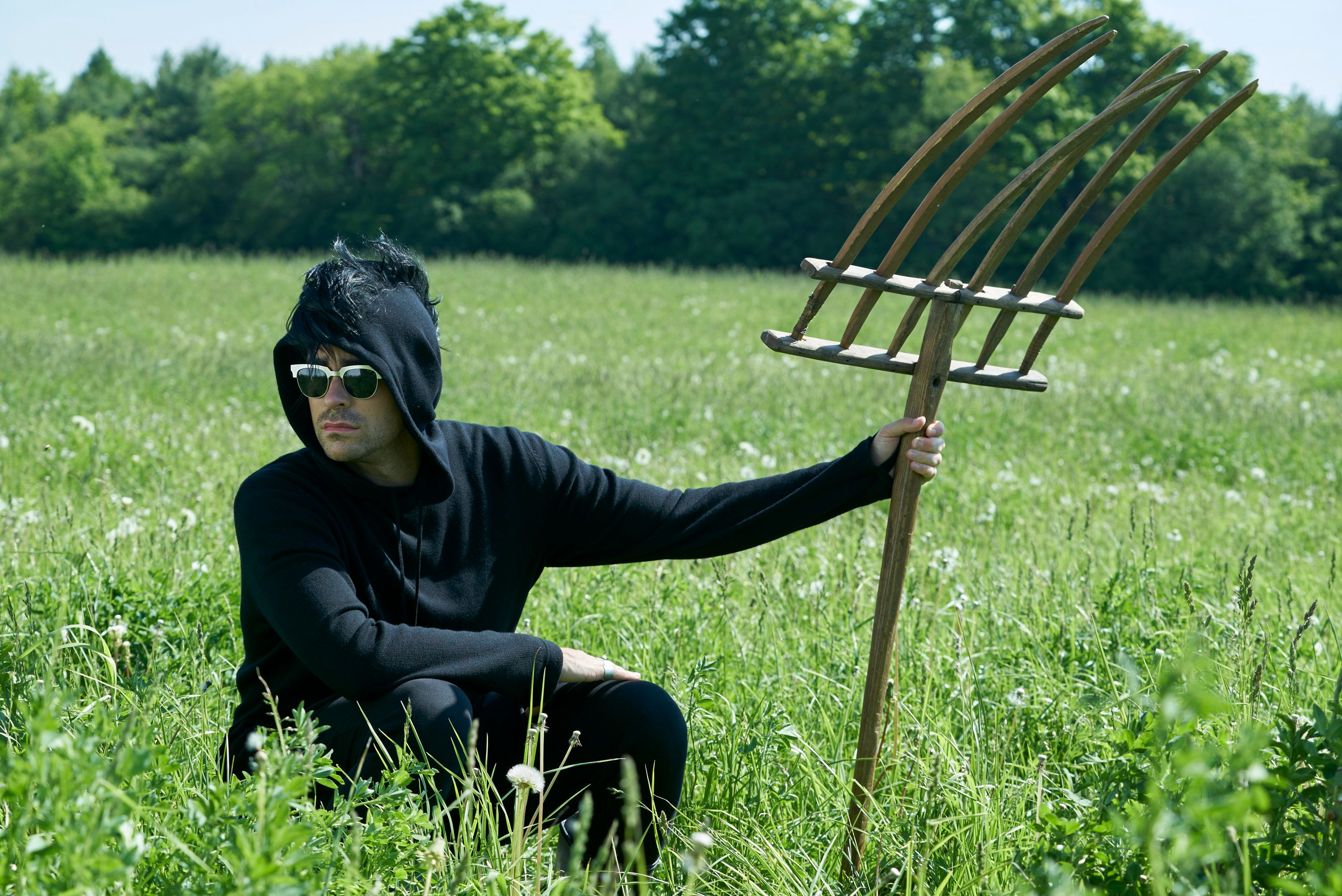 David crouches in a field holding a pitchfork and wearing a black hoodie with faux hawk