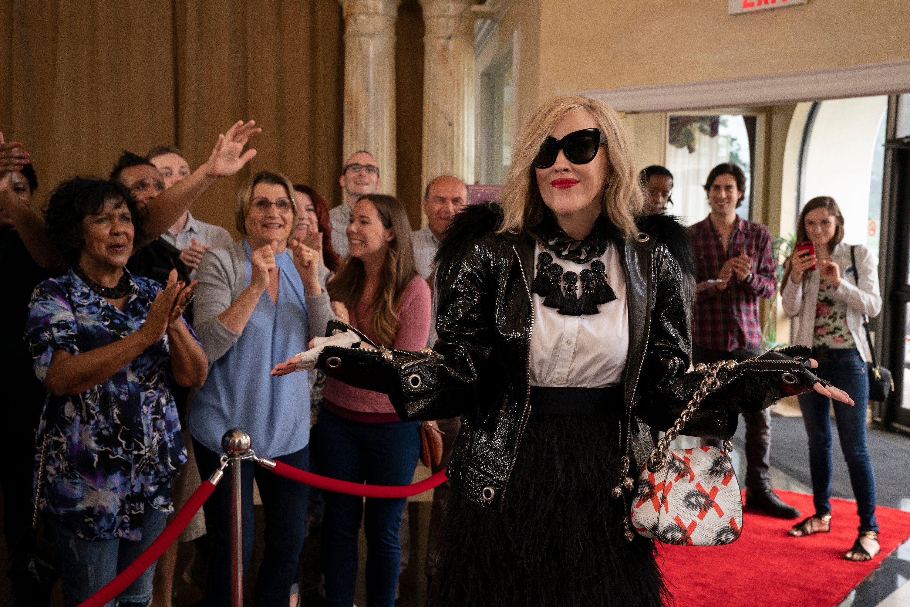 Moira poses on the red carpet while adoring fans admire her from behind a velvet rope