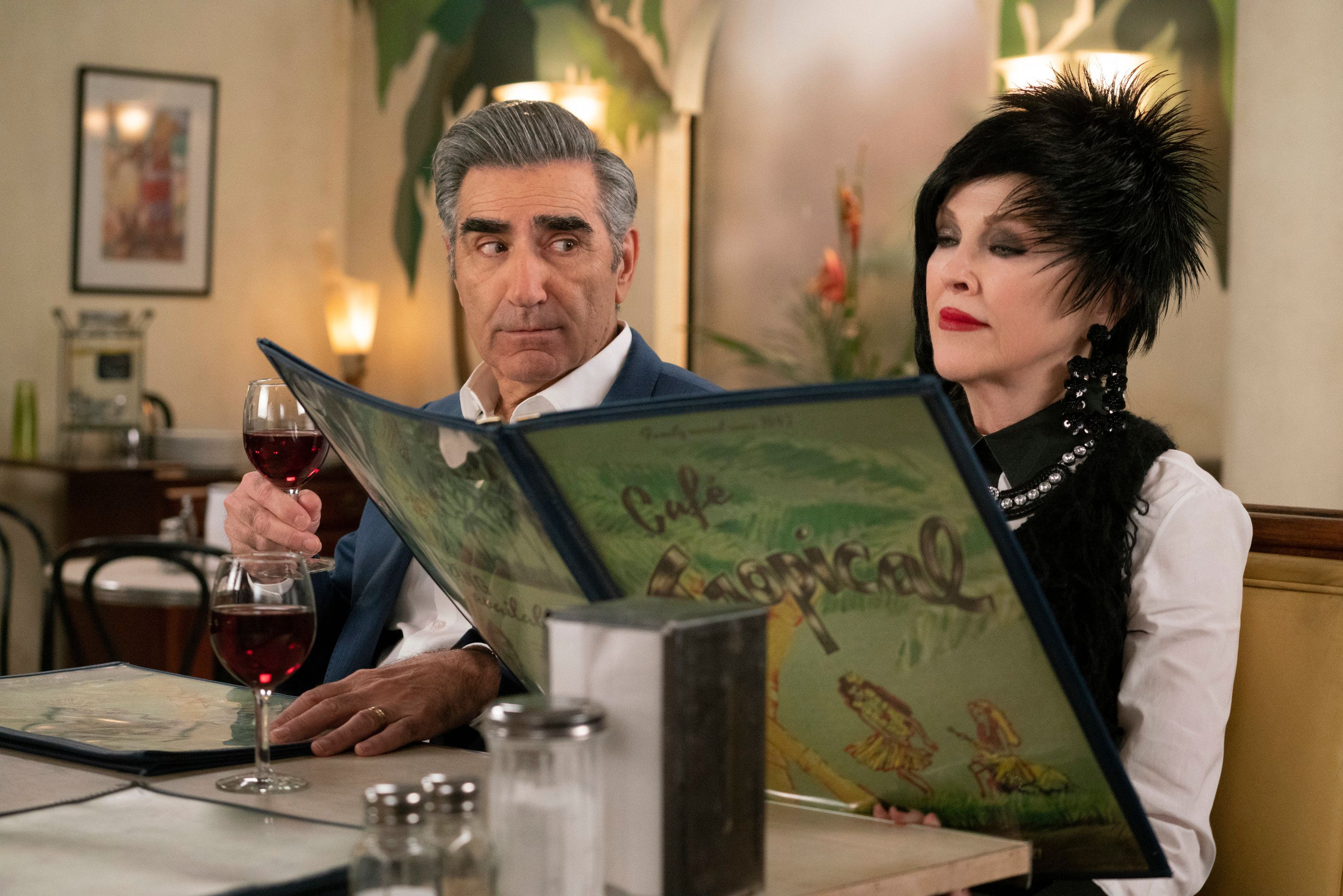 Johnny looks on as Moira peruses the menu at Cafe Tropical