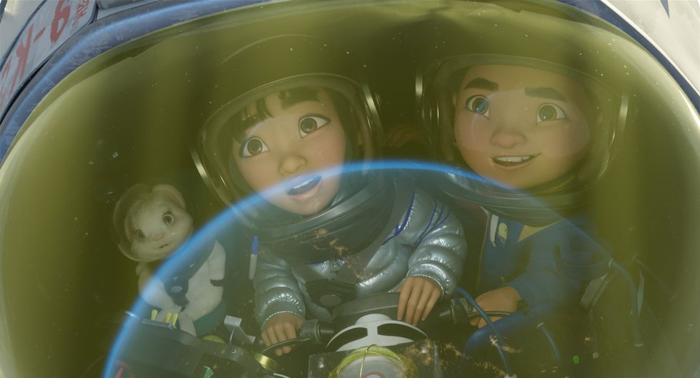 (Left to right) Pet rabbit Bungee, main character Fei Fei and her soon-to-be brother Chin are in a small, handmade space ship. They're all staring in awe of a beam of light that's carrying them toward space. They're all wearing astronaut helmets, with Fei Fei specifically in a homemade space suit. The film still image is a tight shot.