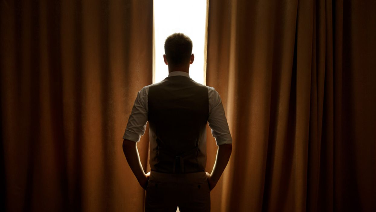 man standing in front of curtains