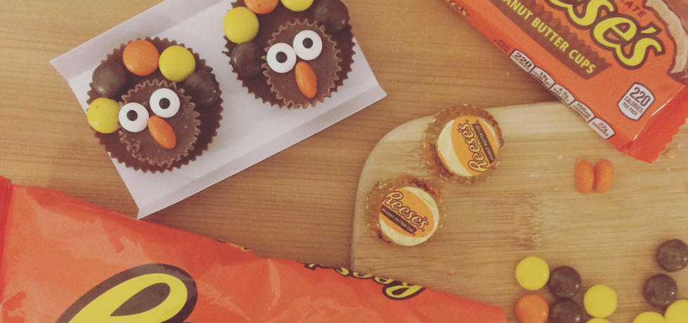 two peanut butter cups with eyes and a nose made out of candy to look like turkeys
