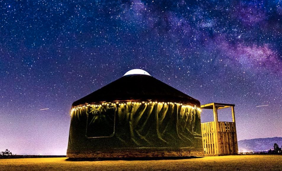 A circular yurt-style home at night with a star-studded night in the background