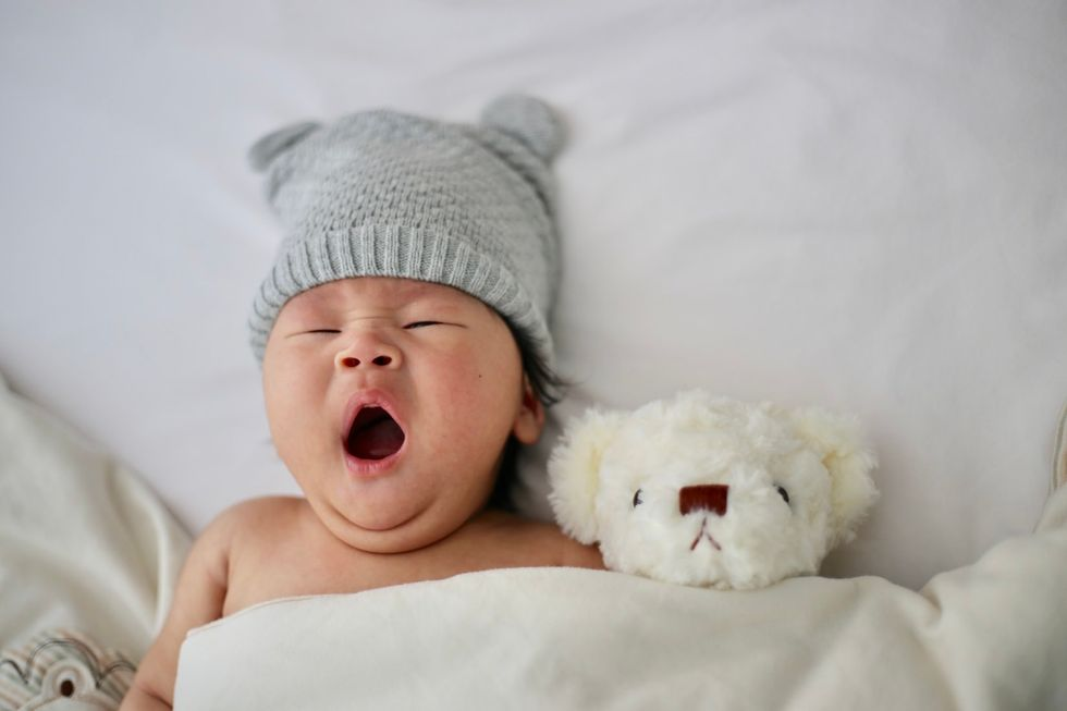a baby wearing a grey sock hat yawning, covered in a white blanket