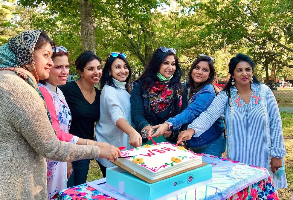 7 women outside surrounding a cake and smiling