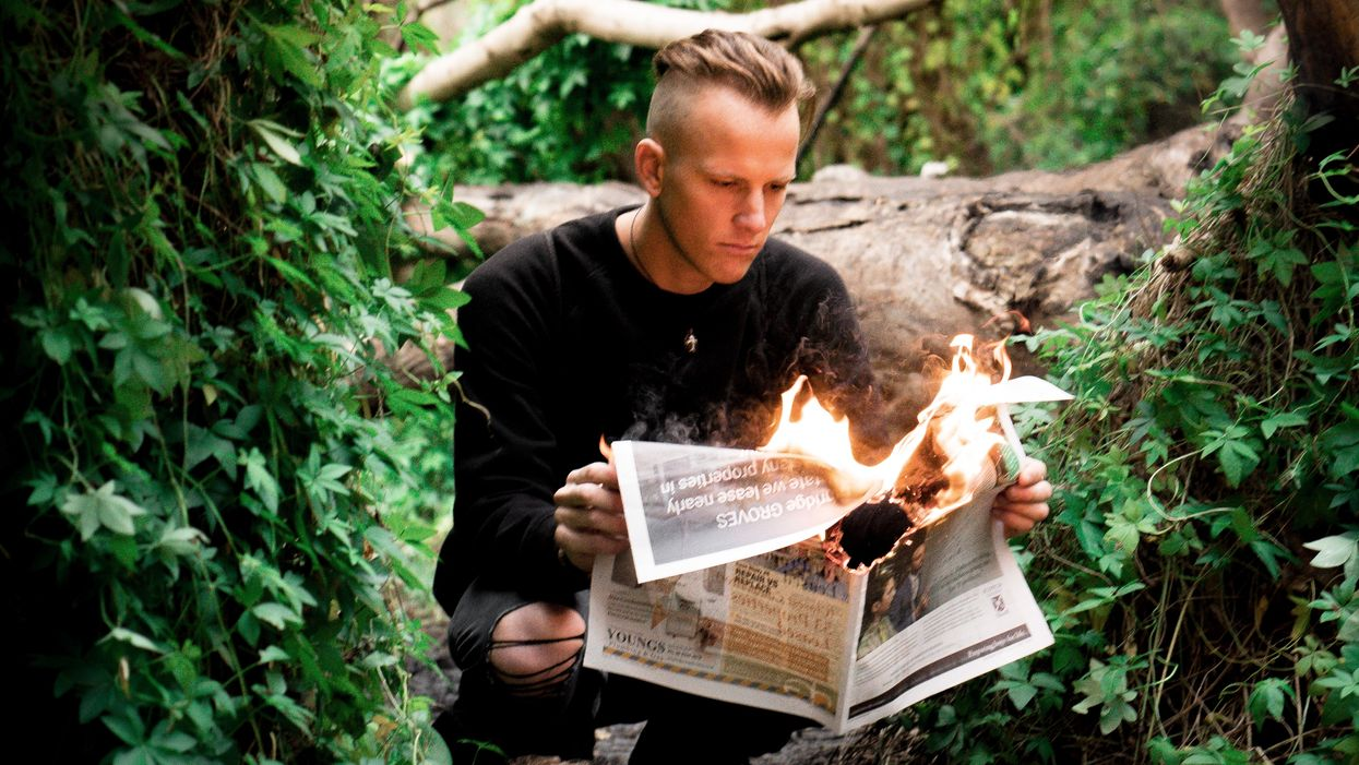 fake holding newspaper on fire