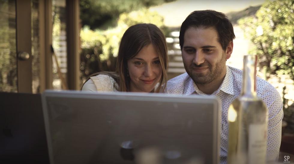Couple staring at computer during virtual Zoom wedding celebration