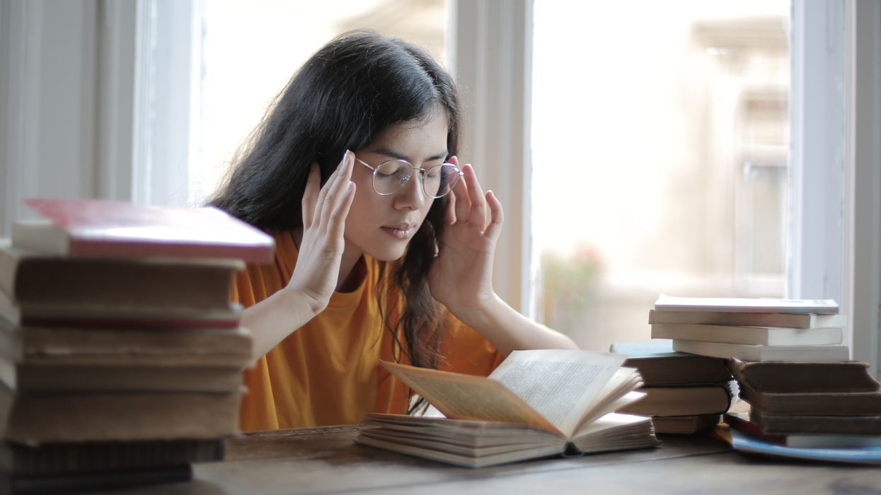 mentally exhausted woman with books