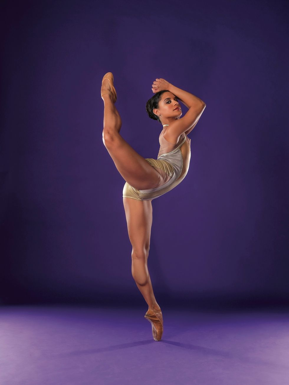 Tatiana Melendez, wearing a shiny gold leotard, stands on her left leg on pointe and kicks her bent right leg head height behnd her.