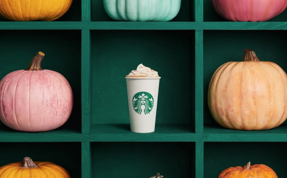 A starbucks cup on a shelf with whipped cream on it, surrounded by pumpkins