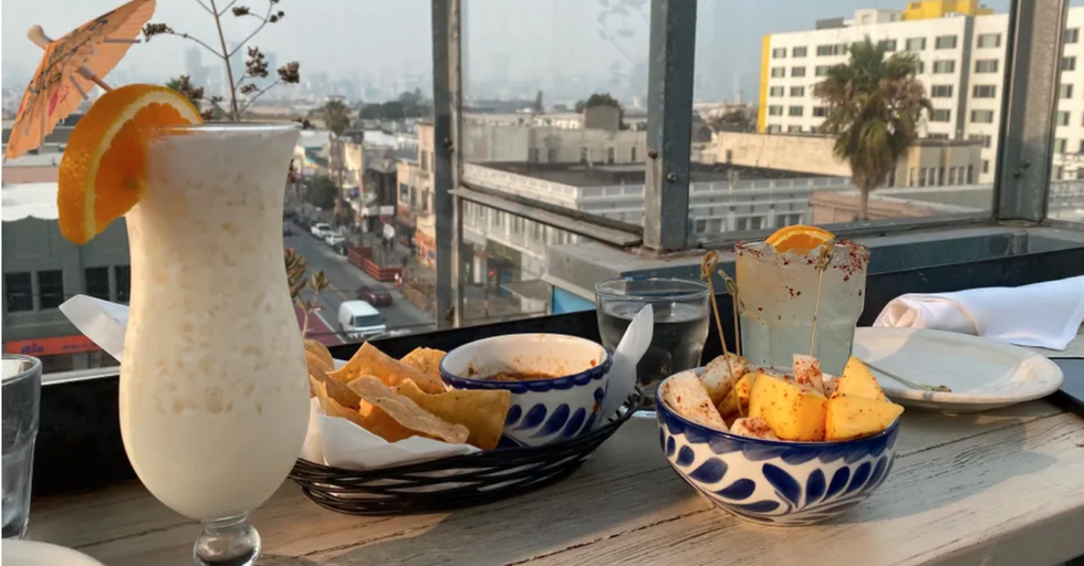 a plate and bowl of food along with two tropical drinks with a view of a city behind them