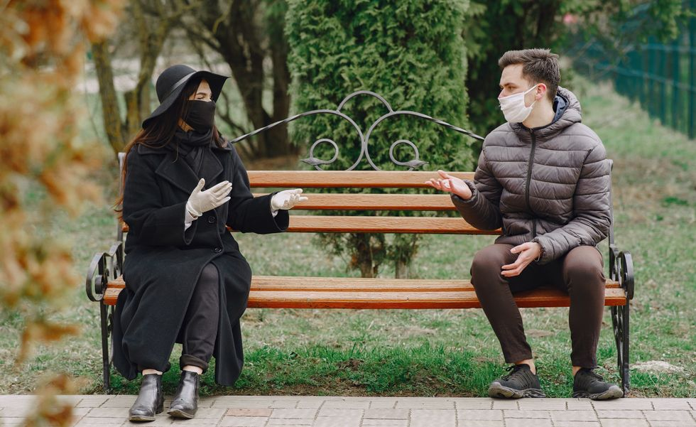 Man and woman wearing masks and chatting while social distanced on park bench