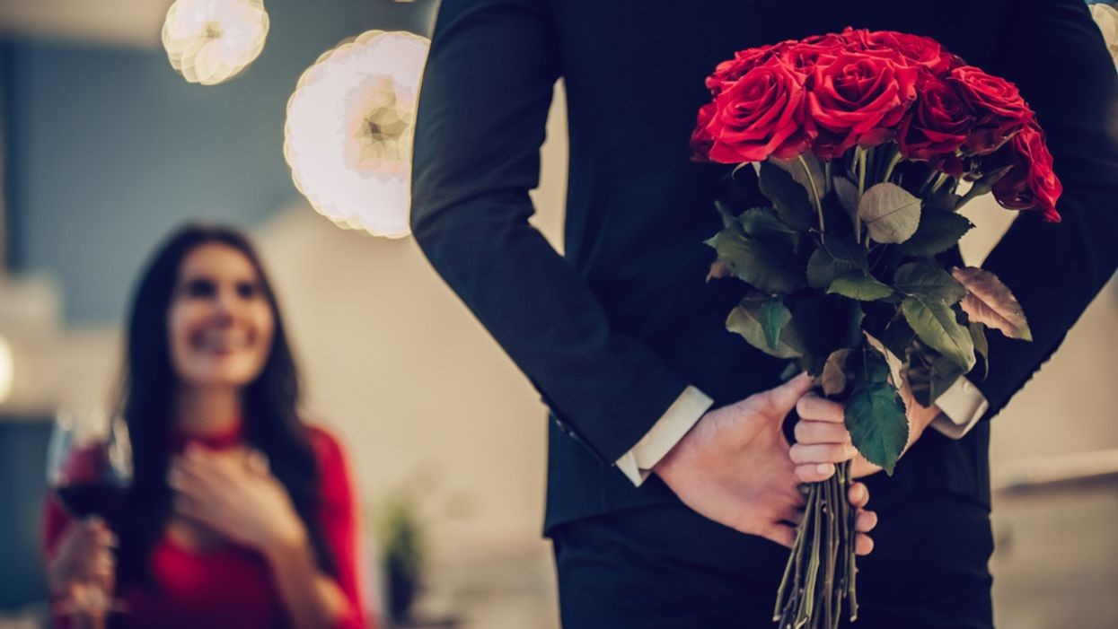 man surprising woman on date with red roses