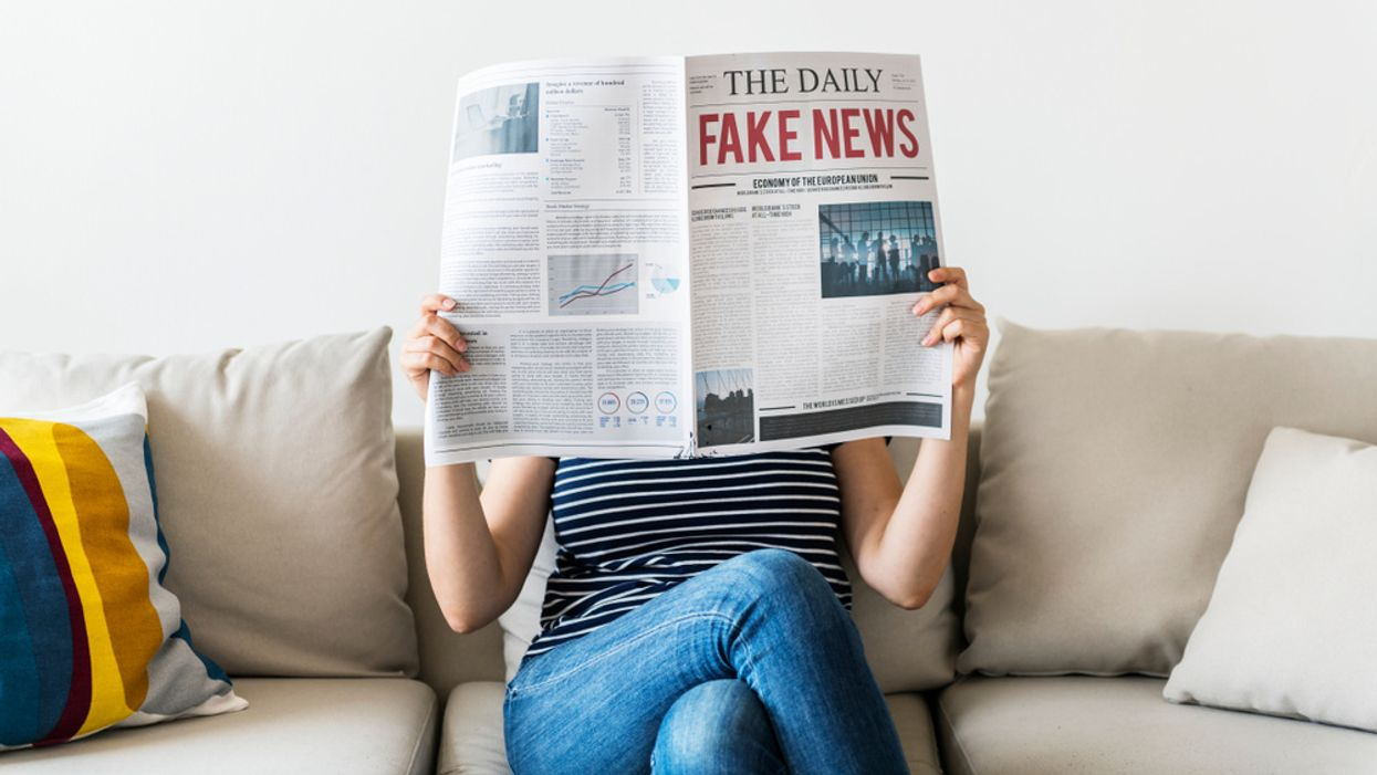 woman sitting on couch reading fake news