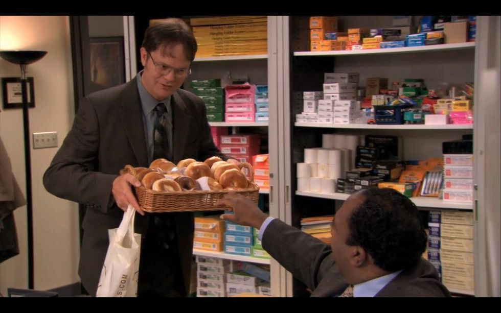 """Dwight from """"The Office"""" holding a basket filled with bagels"""