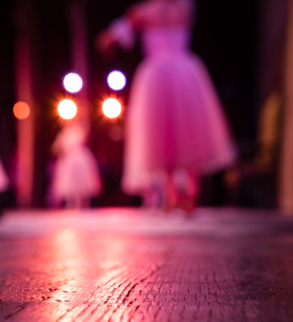 Blurred ballerinas in long white tutus dance on a wooden floor and are viewed from backstage.
