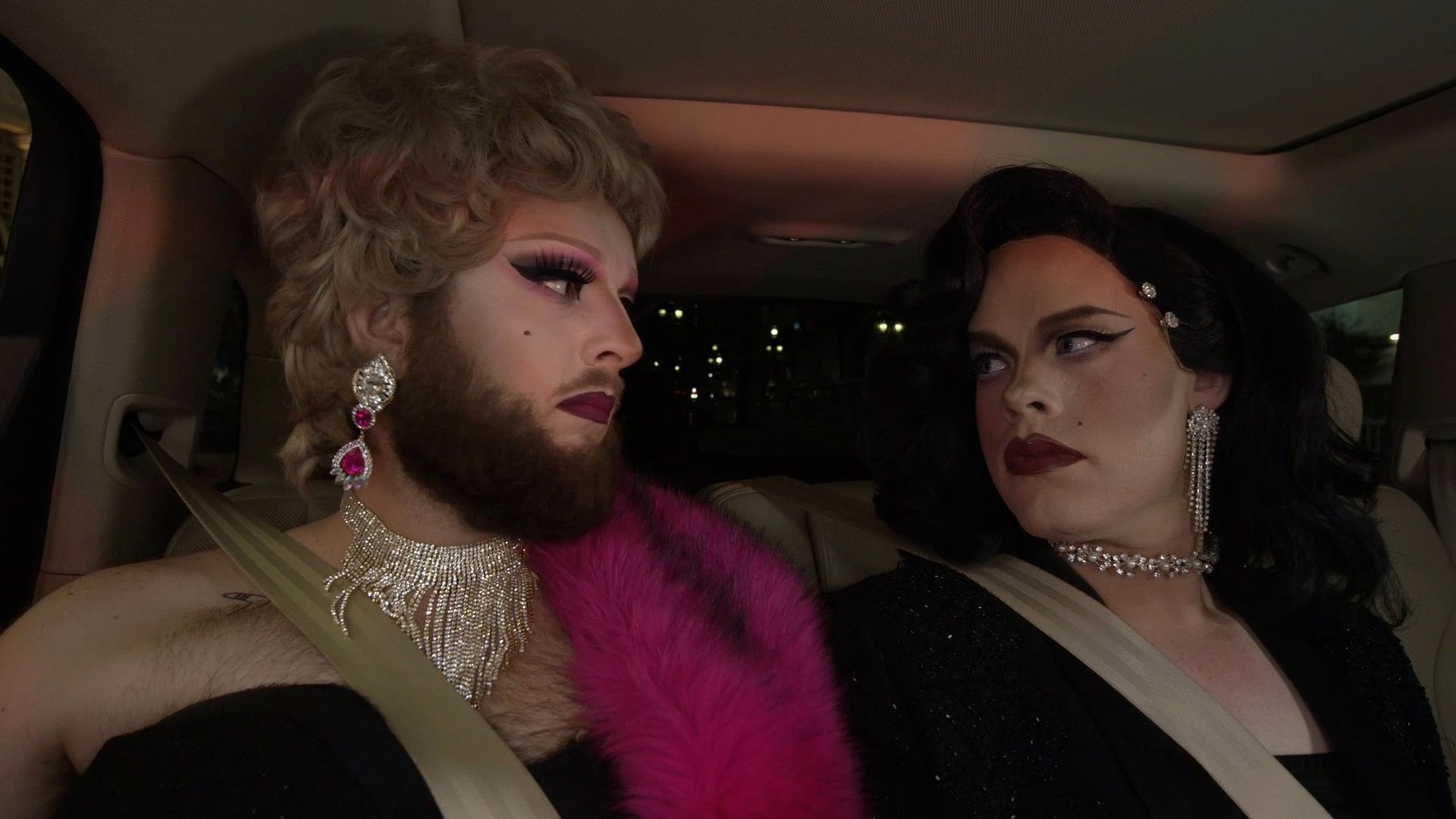 Two drag queens give each other a shocked look