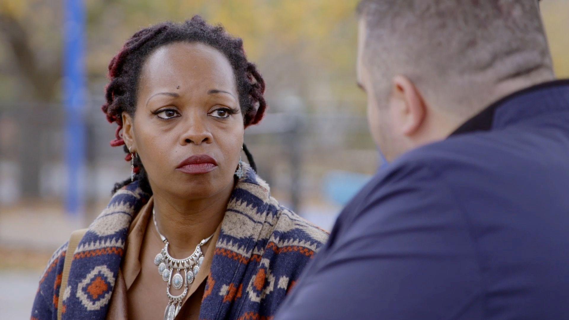 Teary-eyed woman on park bench talks to Thomas John