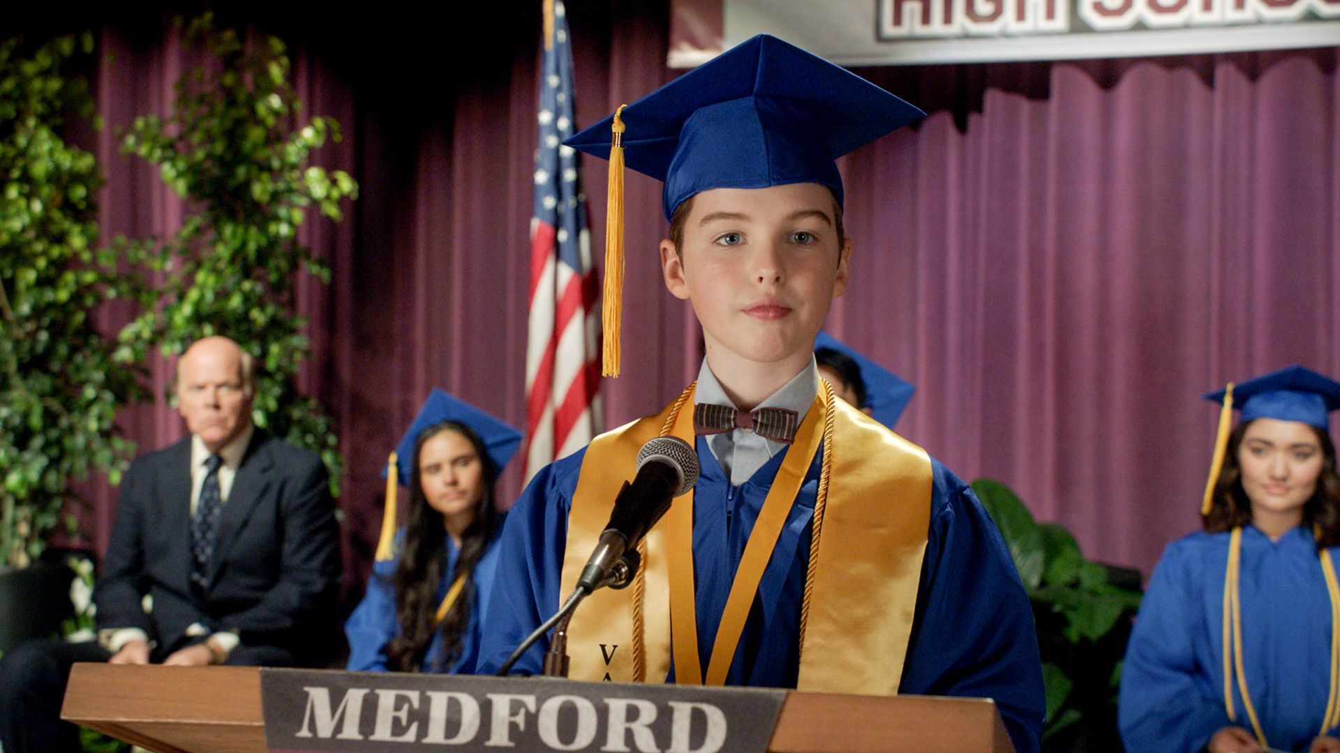 Sheldon in a blue cap and gown at his graduation ceremony