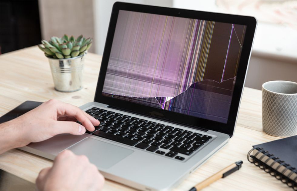 Man working with broken laptop on office background
