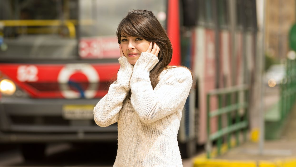 woman covering her ears from noise