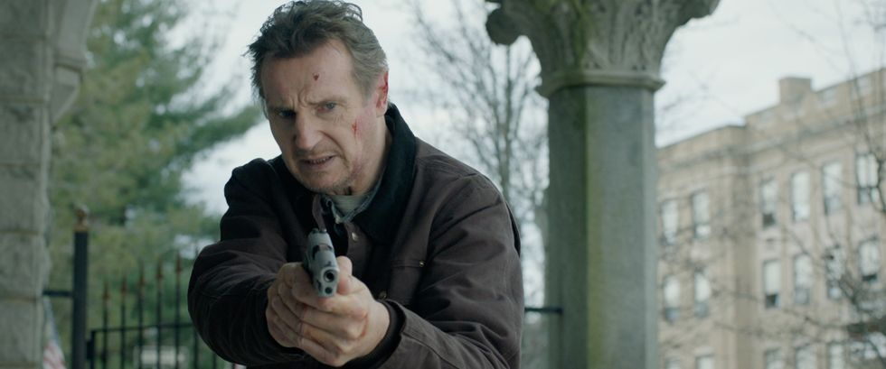 "Liam Neeson as Tom Carter in ""Honest Thief."" He's wearing a brown jacket and about two additional layers of clothing. He's pointing a pistol toward a suspect on the floor. In the background, he's in a suburban area with iron fences and both leaf-less and full trees."