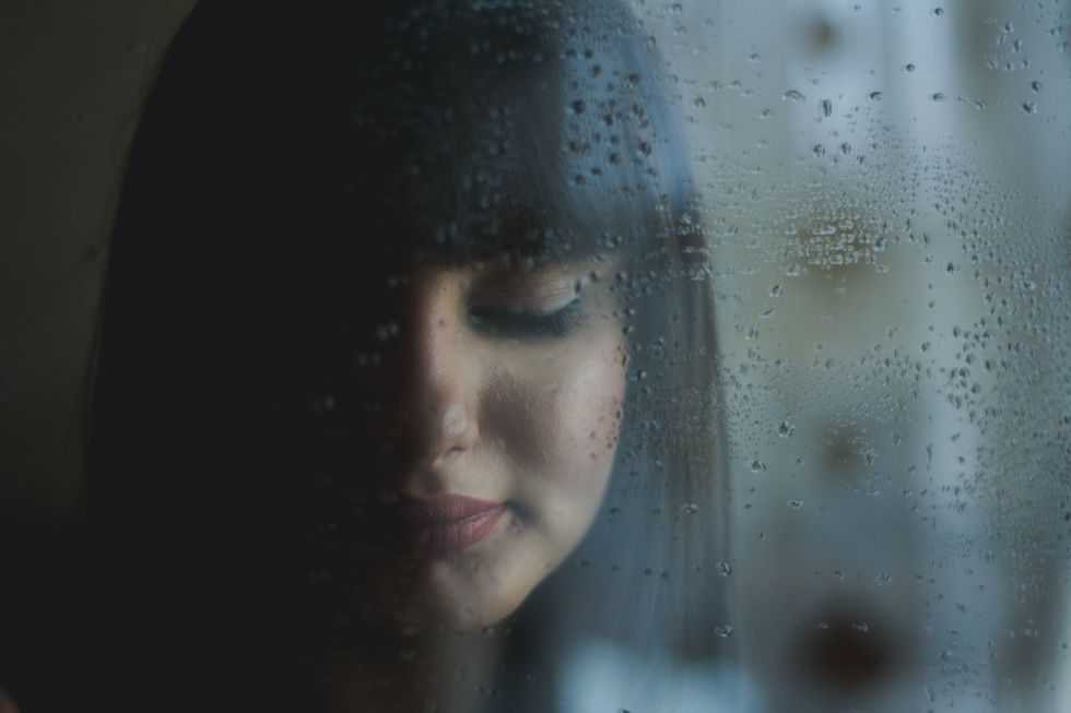 Girl staring out window at rain