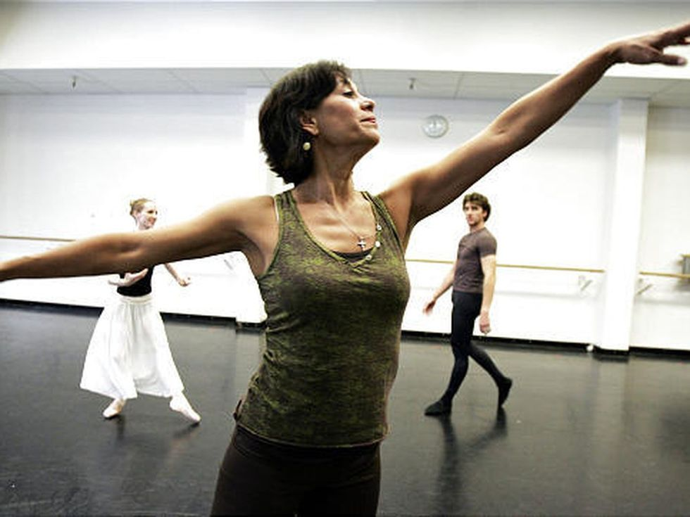 Evelyn Cisneros-Legate demonstrates first arabesque arms, limbs stretching beyond the edge of the photo, as a male and female dancer in rehearsal clothes watch from the back of the studio.