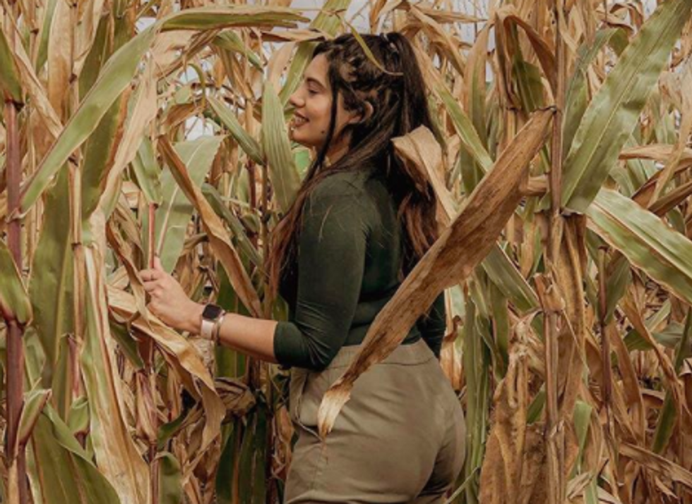 person standing in field of corn, smiling