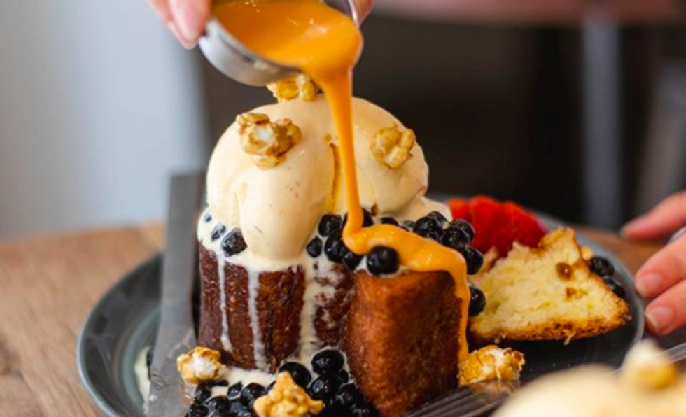 a cake topped with ice cream and bluberries with someone pouring an orange sauce over it