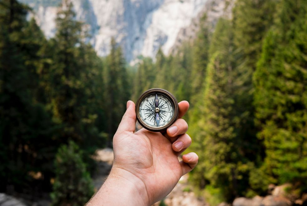 person holding up compass in a forest