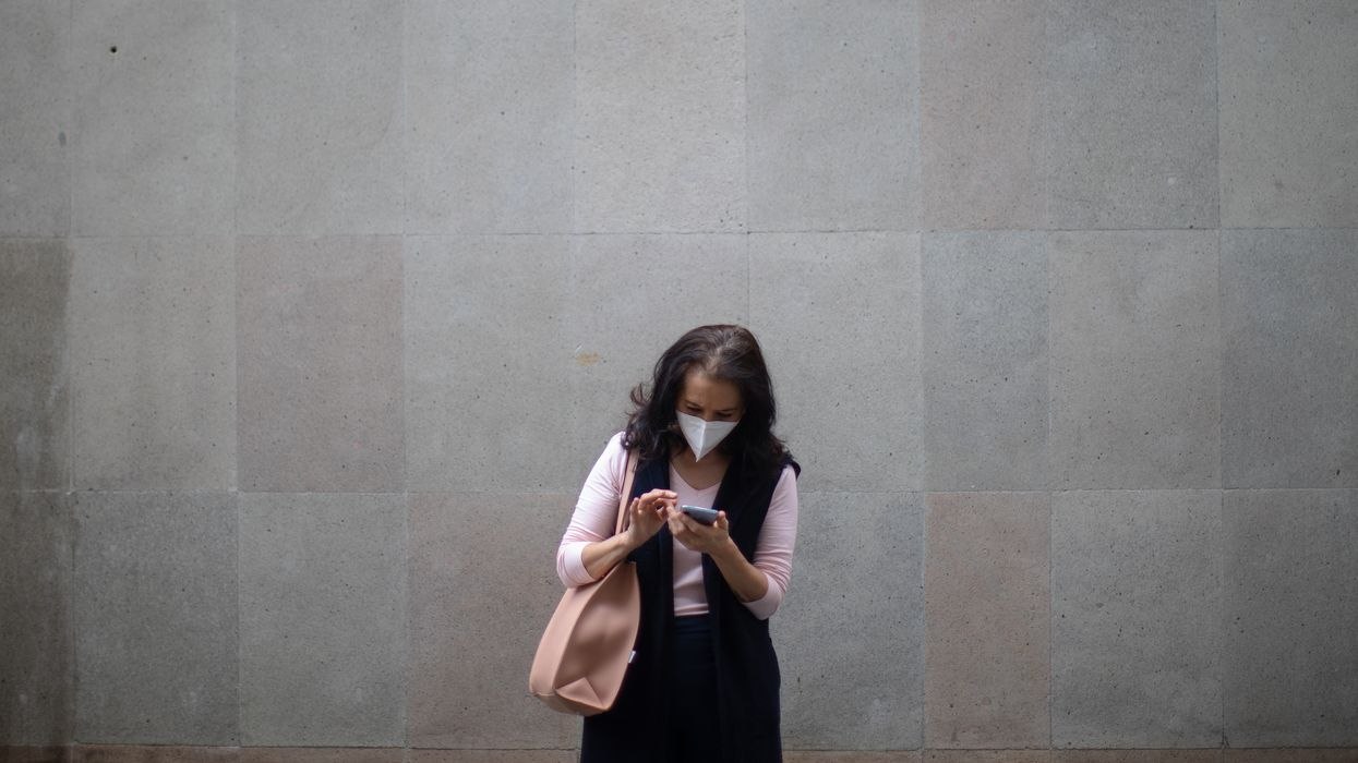 A woman uses her phone while wearing a face mask on October 08, 2020 in Mexico City, Mexico.