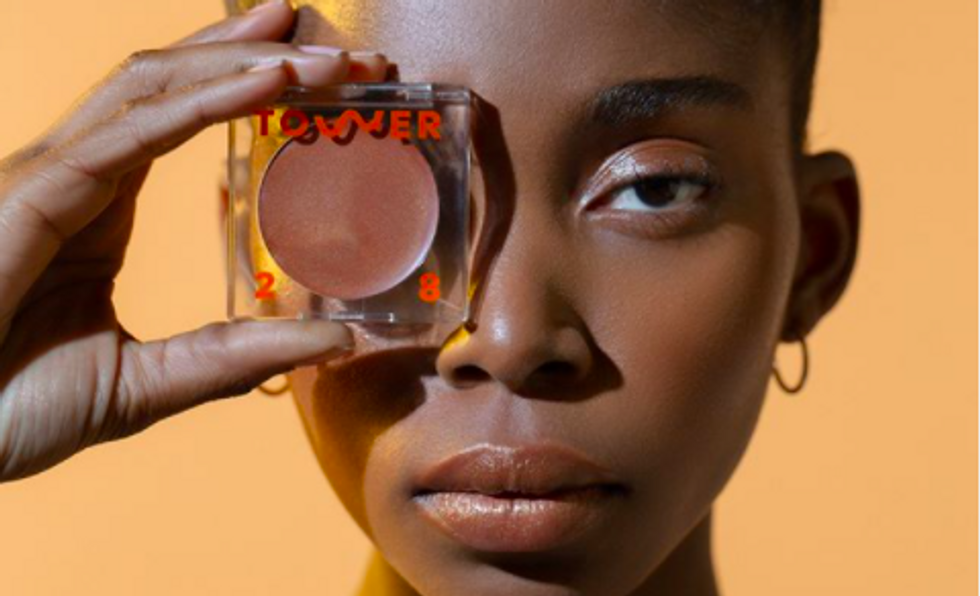 "someone holding a bronzer with ""tower 28"" written on it over their eye"