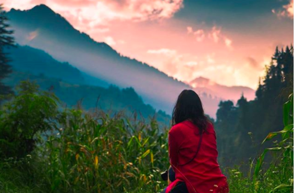 someone sitting in grass, looking out at mountain landscape
