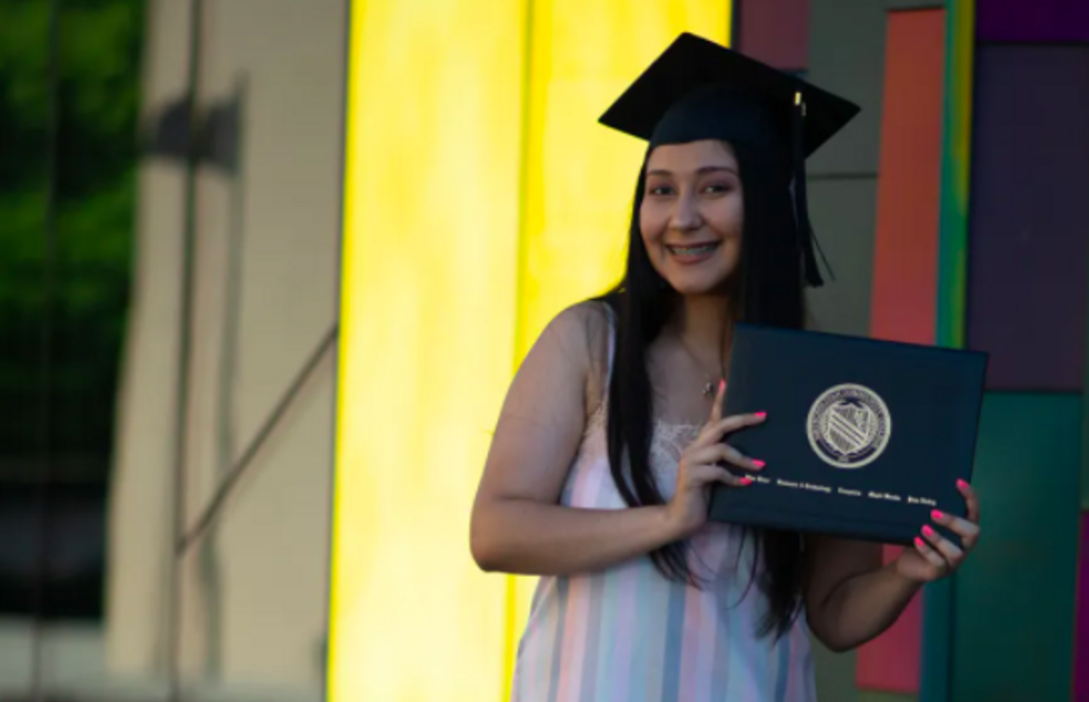 me holding a picture of my diploma with a graduation hat on