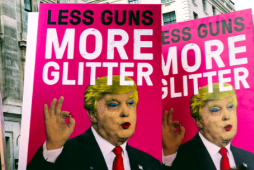"""pink signs reading """"less guns more glitter"""" with trumps face on them, painted with makeup"""