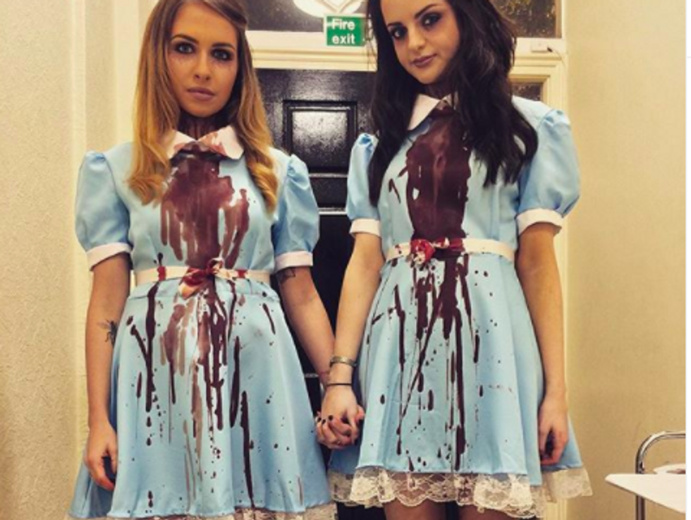 two people wearing blue dresses covered in red stains