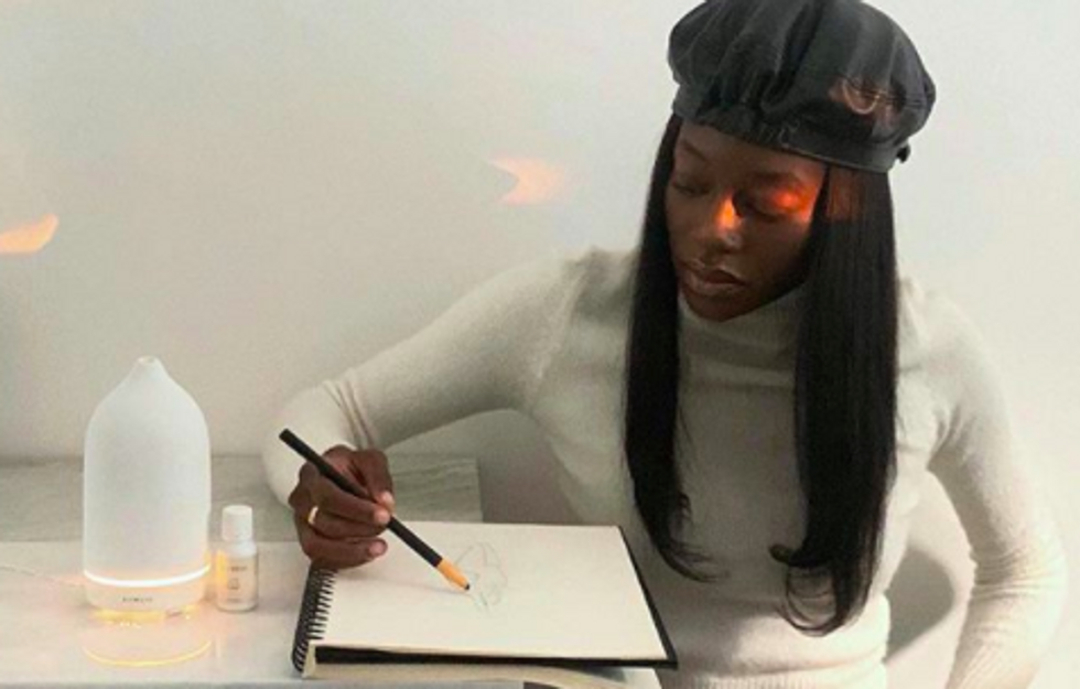 stylish person sketching in a notepad with an oil diffuser next to them