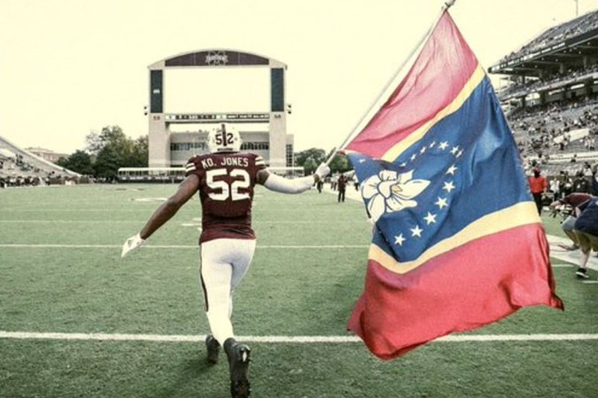Mississippi State player proudly waves the state's new Confederate-free flag on game day