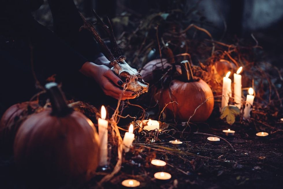a scene of candles, pumpkins, and a pair of hands holding the skull of a horned animal.