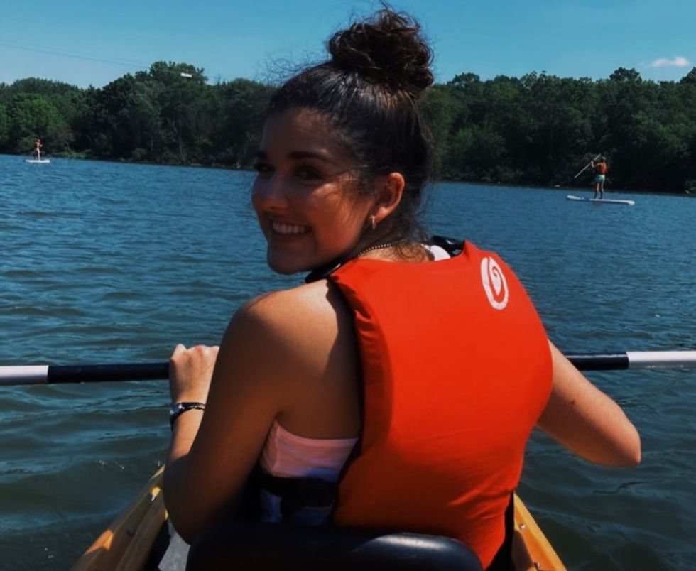 Young female college student kayaking in lake during the summer.