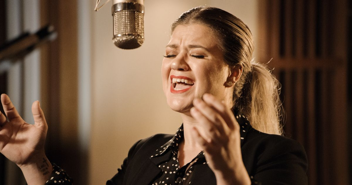 Kelly Clarkson singing at a microphone