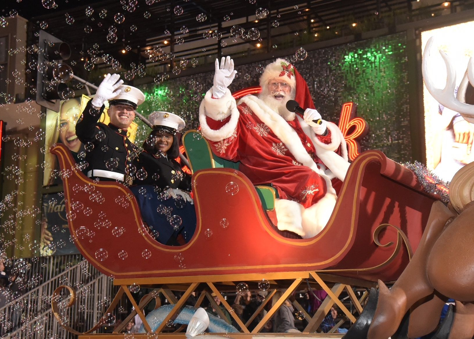 \u200bSanta Claus and service members wave from the sleigh