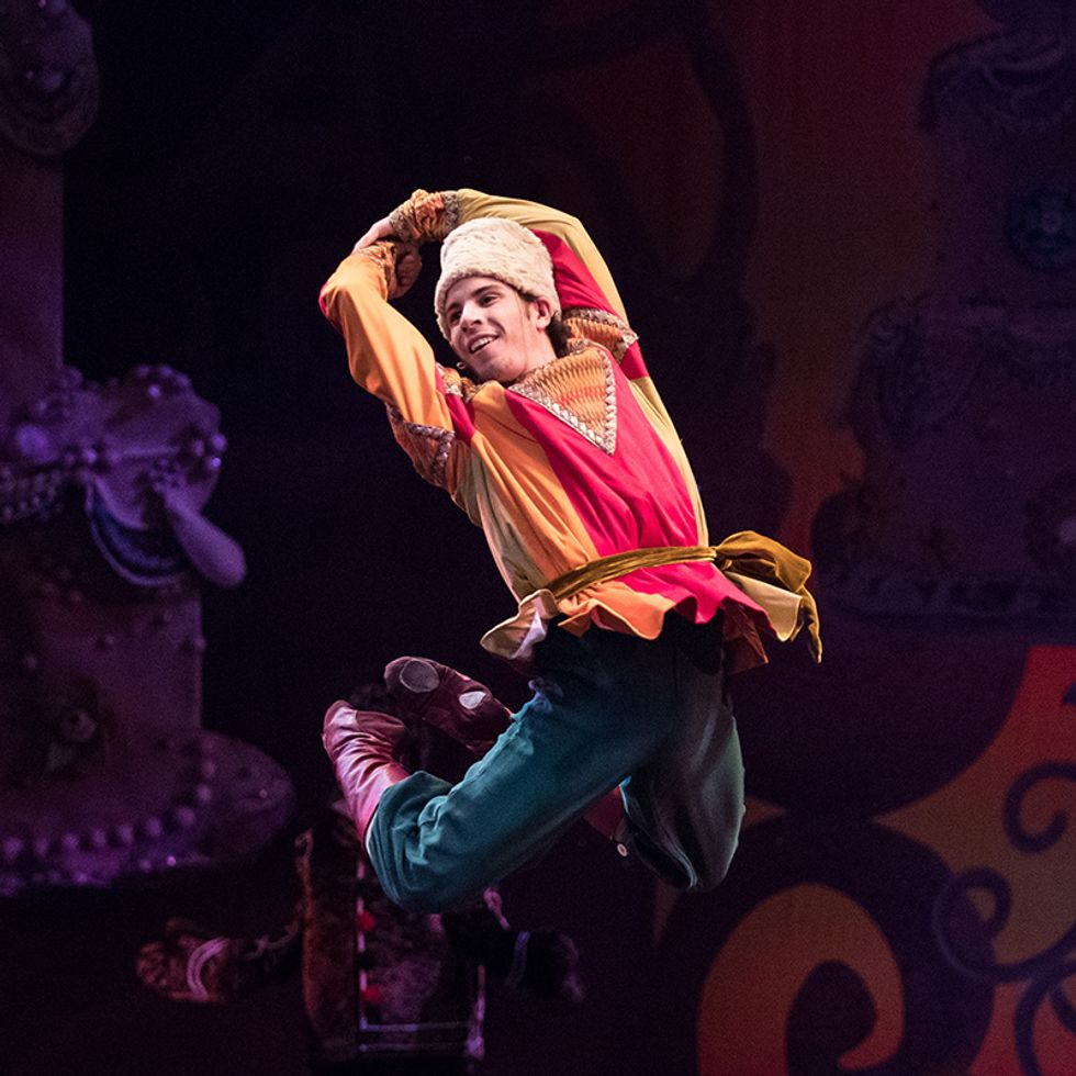 Taylor Carrasco, in a colorful Russian folk costume , white furry hat and purple boots, arches his back and jumps with his legs bent back behind him and his arms clasped over his head.