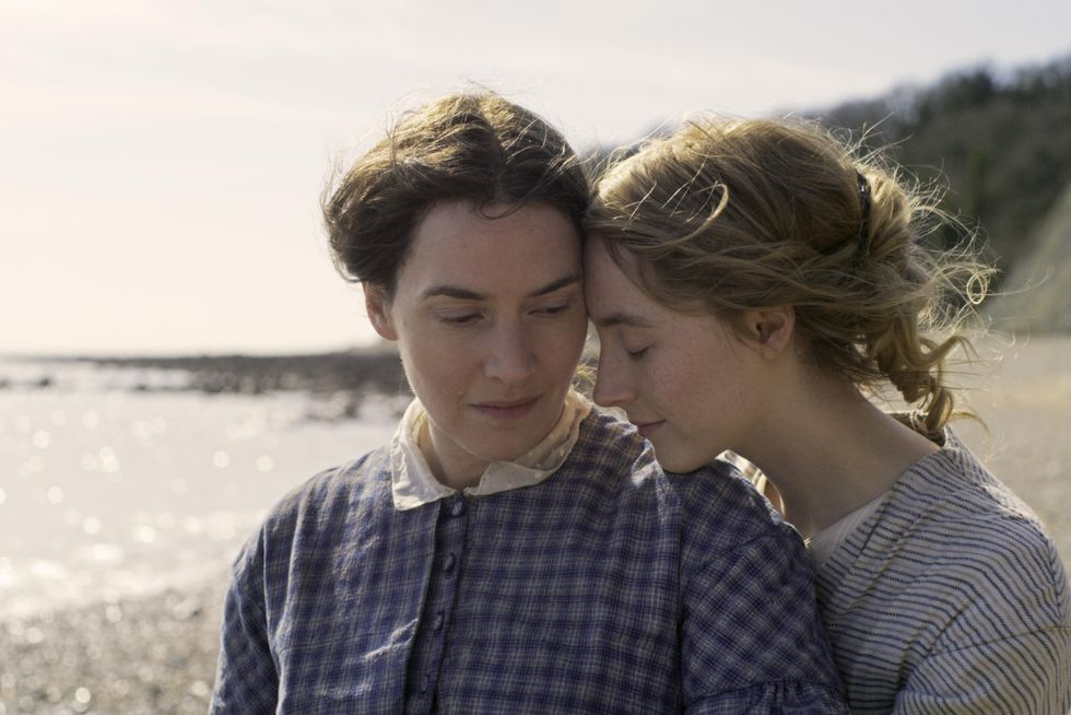 The photo is a close up shot of Kate Winslet (left) as Mary Anning and Saoirse Ronan (right) as Charlotte Murchison. Saoirse has her forehead to the side of Kate's and Saoirse rests her chin on Kate's left shoulder, with her eyes closed. Both are wearing casual period clothing from the late 1800s England. The Southern Shore is shown, blurred, in the background.