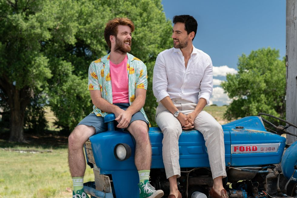 "Connor Del Rio (left) as ""Asher"" and Luis Gerardo Mendez (right) as ""Renato"" in ""Half Brothers."" Connor is wearing a button down short sleeve shirt with rubber ducks on them and a pink shirt underneath it. Blue shorts and green socks and converse. Luis is wearing a dress shirt, slacks and moccasins. They're looking at each other, laughing and sitting on a small farming tractor. In the background, it's green and bright. It looks like a farm."