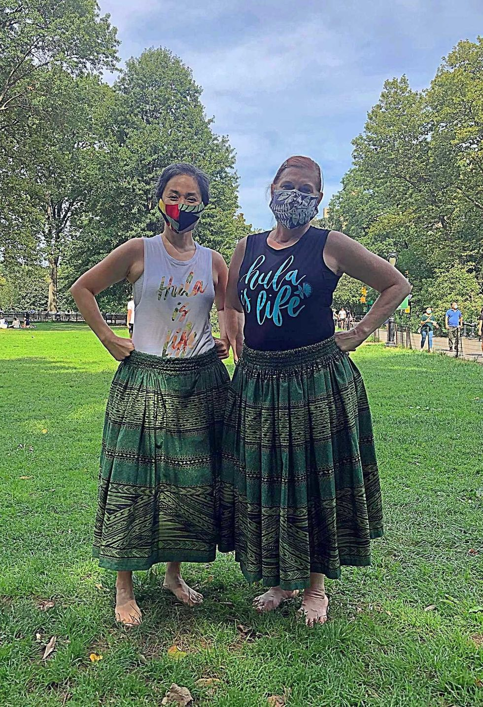 "Two women in green skirts, masks, and shirts that say ""hula is life,"" stand in a grassy area in the park"